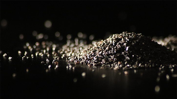 Image is of a pile of Macrogrit Brown Aluminum Oxide abrasive on a black backdrop.