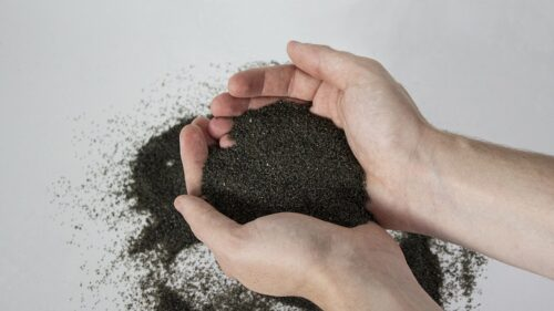 Image is of a pair of hands holding a pile of 10X Abrasives. The abrasives are a dark gray.