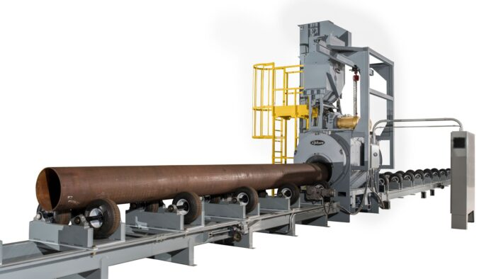 Image is of a large piece of machinery being fed a large cut of pipe to be blasted inside a wheel blast chamber. Machinery is grey photographed on a white background with a rusty pipe being rolled into it.