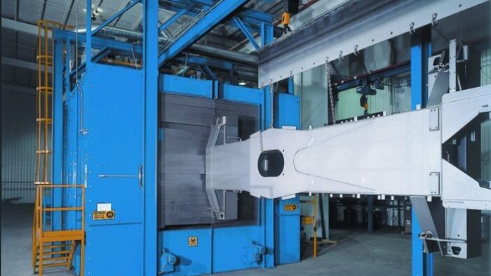 Image is of a large piece of equipment with a wheel blast corrider being fed a large work-piece via an overhead monorail system.