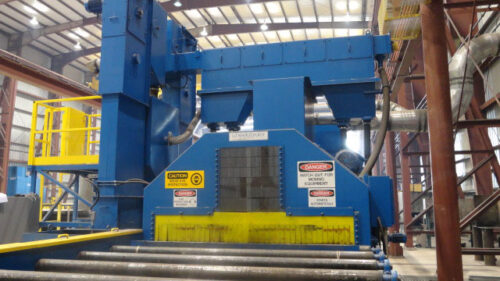 Image is of a piece of blue and yellow machinery with a large wheel blast corridor that is fed by a roll conveyor system. The machinery was photographed within a warehouse.