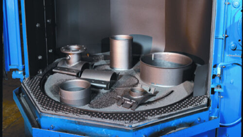 Image is of the interior of a blue table wheel blast machine with the compartment open showing just blasted metallic work-pieces.