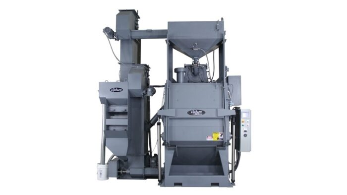Image is of a Gibson tumble wheel blast system. It is a grey piece of machinery on a white background.